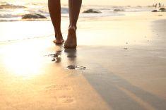 Girl walking on wet sandy beach leaving footprints stock photo. Great shot for BAREFOOT BEACH!