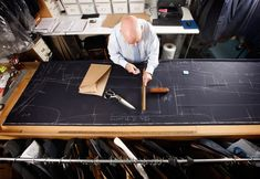 Bespoke Head Cutter Peter O'Neill marks out and cuts a suit pattern at Gieves and Hawkes on Saville Row on August 13, 2008 in London, England. A bespoke two piece suit takes up to eight weeks to make and start at around 3500 GBP