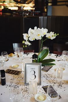 Simple and elegant single orchid as a centerpiece with table scatter and votive candles More