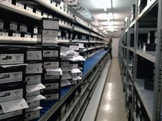 Mittels Lagerentnahmescheinen werden die einzelnen Schuhkartons aus den Regalen entnommen und pro Kunde auf einem Rollband gesammelt.