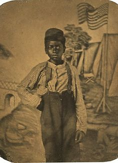 Tintype of black child standing in front of Civil War camp backdrop.