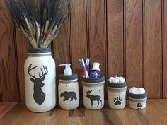 Add some rustic charm to your bathroom or kitchen with this woodland mason jar set! This 5 piece Ball Mason Jar Set is hand-painted, distressed and sealed with a matte sealant. The moose, deer, bear, bear paw and buck print are hand painted on. ***IF YOU HAVE A DIFFERENT THEME OTHER THAN THIS, PLEASE LET ME KNOW AND I WILL MAKE YOUR MASON JAR SET FOR YOUR THEME :) !! I love custom orders :) The set includes Mason Jar Soap Dispenser for your choice of soap, lotion, sanitizer, etc. with a…