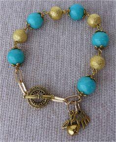 Pulseira com contas em azul e douradas, fecho dourado e peças douradas em forma de mão maça.  Visite: http://artebijuarmanda.blogspot.pt