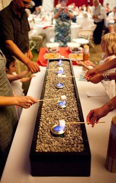 Why not have s'mores at your wedding. Here is a simple way to bring the campfire to your reception venue. The base is a wooden box filled with pebbles. The flames are cans of Sterno. You could also use sea glass as a filler.