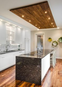 This inviting kitchen features flat-front white cabinets paired with black granite countertops and a neutral accent wall. A wood paneled ceiling accent with recessed lighting is positioned above the spacious island area, which includes stools for casual dining.