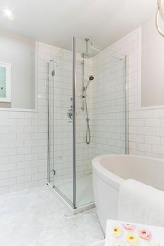 A stainless steel corner shower enclosure opens to a shower filled with large white subway tiles fitted with two shower heads placed next to an oval freestanding bathtub. Corner Shower Tile, Corner Shower Enclosures, Bathroom Shower Heads, Glass Shower Doors, Small Bathroom, Master Bathroom, Shower Tiles, Light Grey Bathrooms, Gray And White Bathroom