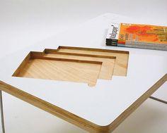 living in desingland/es una ingeniosa mesa-revistero diseñada por la artista Sarah Huston, en cuyo sobre se han realizado tres huecos para poder tener cómodamente a mano y colocar de forma ordenada nuestras tres últimas revistas preferidas.