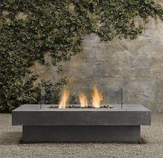 Restoration Hardware's solution to the outdoor fire pit.  Love it, plus the glass around the fire to keep us from burning down the house.