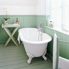 To achieve a cohesive look in this serene cottage-style bath, the pine floorboards, baseboards, and wainscoting are painted a similar sage-g...