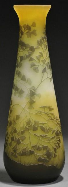 glass, France, A tall Galle Cameo art glass vase, France, 1918 to 1936, flared rim on swollen cylindrical form cameo decorated with fronds and fan shaped leaves on olive green glass cut to lighter shade of green with yellow shading a rim, signed