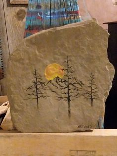A painting on rock, mountains trees and a setting sun art by Stacie Sheets