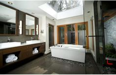 Love the dark grays and browns.  The huge skylight is wonderful; would be an excellent alternative to big windows (with nosey neighbours) to bring the outdoors in.  Looks like a smoke glass is used for the shower, nice touch.  Like the contrast between the main tile and the tile/rocks under the tub to define the space.  If rock tiles, might be a bit challenging to clean tho.. ; )