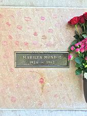 "Photo of Monroe's crypt, taken in 2015. ""Marilyn Monroe, 1926–1962"" is written on a plaque. The crypt is covered in lipstick prints left by visitors and pink and red roses are placed in a vase attached to it."