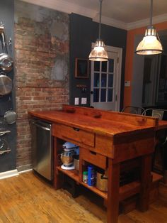 Antique workbench as kitchen island with exposed brick chimney - retrofitted for dishwasher. Antique mogul socket barn lights. Breakfast bar off back is a reclaimed barn floor.