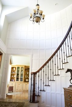 wainscoting, wood rail with iron in this style home is atypical but it works well!