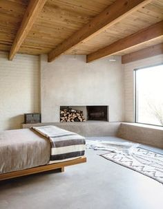 Local furniture maker Nate Danforth built all of the house's cabinetry, as well as the master bed, which is teak. The fireplace wall is plaster, the hide is reindeer, the Navajo rug is from the 1920s and the brushed-nickel lighting is by Modulightor and designed by Paul Rudolph. Credit Stefan Ruiz