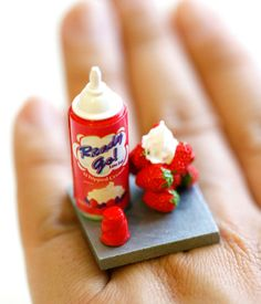 A super cute strawberry whip cream bottle with some strawberries. There is even some whip cream on the strawberries!! How cute is that!!