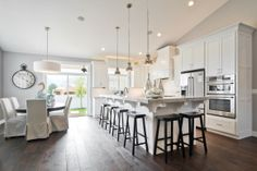 White kitchen, dark floors. Too many stools for my liking. Great low hanging lights. Open plan. Large Island bench, great for the heart of the home. Homework, Parties & heart-to-hearts over a glass of wine.