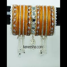 Vibrant Bangle Set in Fiery Orange and Silver Color  A glinting set of bangles in fiery orange and silver. The fiery orange plain bangles are teamed with those dotted with silver sparkle. The silver beaded bangles exude brilliance with dangling silver chains. The delicately carved silver bangles on the ends add style to this set. A designer kada with a hanging zhumki is placed at the center. Available Sizes: 2.6, 2.8, 2.10  #OrangeSilverColoredBangles #BuyColorfulIndianBangles