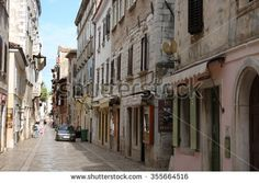 POREC,CROATIA  - AUGUST 20,2015 : Old town street with stores  and walking people on August 20,2015  in Porec  in Croatia. Porec  is a popular tourist town in Croatia.