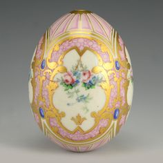 A Russian porcelain Easter egg, circa 1900. The pink egg decorated with gilt scrolls with floral and foliate motifs within four white cartouches separated by blue dots.