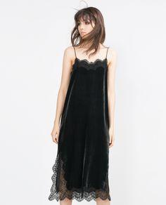 Vestido lencero en terciopelo gris oscuro con largo midi, tirantes muy fino y detalles de encaje negro en el escote y en el bajo de Zara.