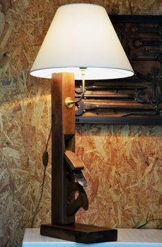 A wooden plane repurposed into a lamp by someone who thinks wrenches are something to be clearcoated and framed. Some points for having a shade. With this much wood, how do you not brutalize the entire thing and hide the cord inside the body instead of having it hang out amidships? This is how you make an Amish Man cry.