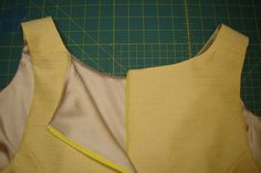 What is a good method for finishing the seam above a zipper? The goal is to have a sharp corner, keep fabric away from the zipper teeth, and reduce bulk. This yellow dress has a lined bodice and inv