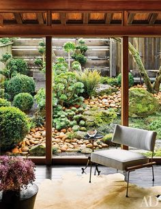 A 1960s chair is paired with a gueridon in the glass-walled office, which offers views of the garden.