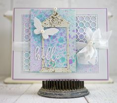 Hi there! It's Mona here today to share a mixed media style card featuring several products from the New Spring 2017 Release along with other fun Poppystamps products. To create the background, I randomly spritzed die cut memory Box Stitched Rectangle Layers with various color sprays. The largerBox Stitched Rectangle features two Ring a Ding Corners layered on top. Once the background was completed, I embellished with a die cut Garden Lantern which I added a coating of embossing enamel that…