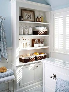 Built-In Storage: Enhance bathroom storage with built-ins. Use open shelves to hold everyday items. Store cotton swabs and cotton balls in glass canisters and keep washcloths in baskets. Stash cleaning supplies out of sight in the lower cabinet.
