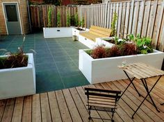 Bamboo deck with grey ceramic tiles and plastered planter with grape vines.