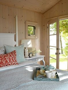 Plank walls and ceiling with white poster bed, nightstand, soft blue bedding, pillow, and a pop of red...Tea anyone?