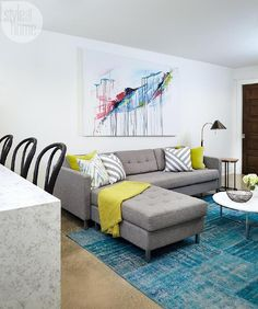 Contemporary basement family room boasts a large colorful abstract canvas art piece hung on white walls above a gray tufted sectional topped with citron yellow and gray diagonal striped accent pillows as well as a citron yellow throw blanket.