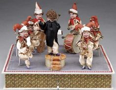 German hand-crank automaton with 7 figures, unknown maker, circa 1920. An outstanding as well as clever automaton, featuring six bisque-headed jester figures playing various instruments, led by bisque-headed conductor.