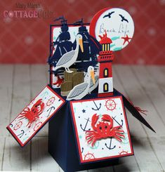 Mary's card using the lighthouse with clouds, crab, large sailboat, pelican, paddles & rope ladder and circle dies