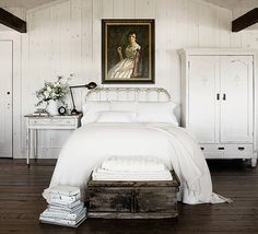 White shiplap walls and farmhouse furnishings clash perfectly with a regal antique oil painting portrait and dark hardwood floors.