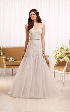 This modified designer A-line wedding gown from Essense of Australia adds the right amount of romance to your wedding day. The fitted, strapless bodice is made from elegant, heirloom-inspired lace. The tulle skirt blooms gracefully into a chapel train. Your choices include clear beading or Diamante embellishments, and a corset closure or an easy-zip back closure under fabric-covered buttons.