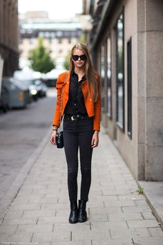 Black outfit with bright leather jacket and a classic black purse handbag.