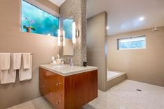 Large mid-century master bathroom with a floating vanity sink lighted by wall lights, along with a drop in tub and a walk-in shower. Mid Century Modern Bathroom, Modern Master Bathroom, Small Bathroom, Modern Bathrooms, Master Bathrooms, Drop In Tub, Open Showers, Corner Tub, Bathroom Photos