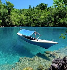The Sulamadaha Beach in Ternate, Moluccas. Crystal clear water makes the boat like floating in the air.