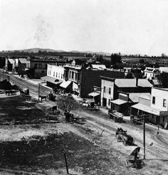 (1880)* - View of Colorado Street, looking west, in 1880. People can be seen walking or riding on horse-drawn carriages, into the town. On the right there is a Lumber yard and a Carpenter's shop. Large building in the distance (left side), is the Ward Block, which includes the Pasadena Bank and the Grand Hotel. Water and Power Associates