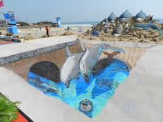 www.tracyleestum.com  Dolphins playing in clean waterways - 3D jugalbandi street painting on pavement and sand sculpture by Sudarsan Pattnaik.    - more at www.streetart.nl #3d #streetart