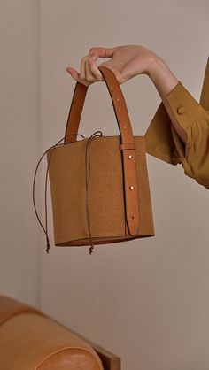 Seed Bucket bag in Tan. Main compartment with adjustable strap, detachable shoulder strap, interior pocket with zipper compartment. Structured bottom.