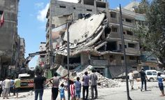 People in Gaza City look at a building destroyed by an Israeli air strike, 19 July 2014