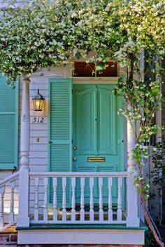 An aqua front door is unusual, but so gorgeous -- especially with gold hardware.
