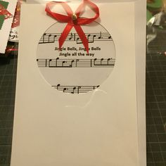 Jingle bells music paper placed in a pre cut card and then a bow and bell were added