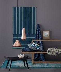"""Damit die Kombination von anthrazitgrauer Wand und petrolfarbenen Textilien nicht zu düster wirkt, haben wir sie mit den Hängeleuchten """"Copper Lights"""" kombiniert. Ihre Kupferoberfläche schimmert auch bei Tage und wirft metallische Reflexe auf Wand und Einrichtung. Das funktioniert natürlich auch mit Vasen oder anderen Accessoires aus Metall."""