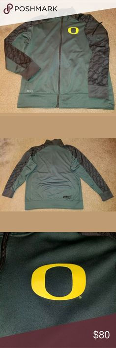 Nike Dri Fit Oregon Ducks Full Zip Jacket Size XL This is a really great pre-owned Nike Dri Fit Oregon Ducks Full Zip Jacket Size XL. It is in excellent pre-owned condition. There are no holes, stains, rips, tears or pulls anywhere in the fabric. It is green, dark gray and yellow in color. The zipper works perfectly. It has a zippered media pocket on the left sleeve for your cellphone. All measurements are pictured. Please review all pictures carefully for condition and measurements.?…