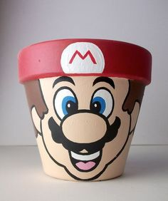 Get creative yourself and make this Super Mario painted flower pot for your geeky loved ones! Flower Pot Art, Clay Flower Pots, Flower Pot Crafts, Clay Pots, Flower Pot People, Clay Pot People, Clay Pot Projects, Clay Pot Crafts, Shell Crafts
